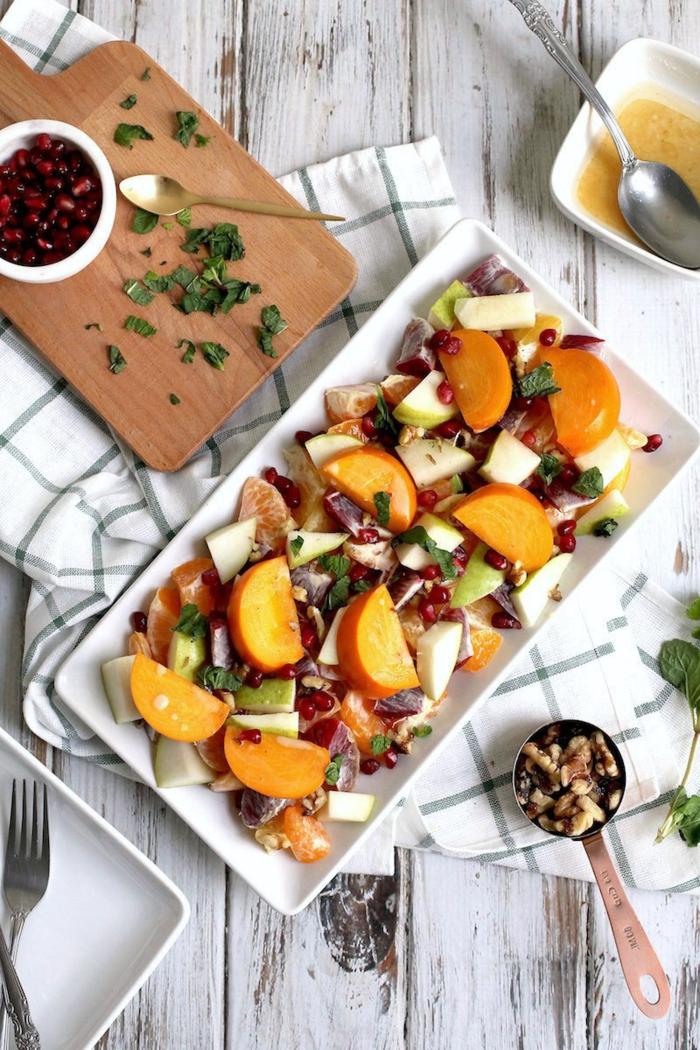 assiette blanche, kaki, pomme, noix de noyers, garniture de graines de grenade sur une planche à découper, nappe aux carreaux