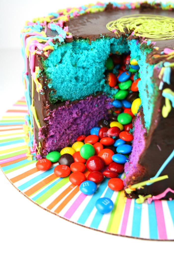 idée de gâteau d'anniversaire fait-maison, gateau smarties recouvert de ganache composé de deux couches de génoise de couleur bleu et violet qui renferme des bonbons