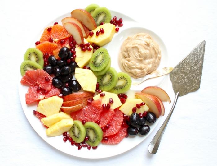 salade de noel avec garniture de camembert, jolis fruits regroupés et arrangés sur une assiette blanche, kiwis, pommes, pamplemousse