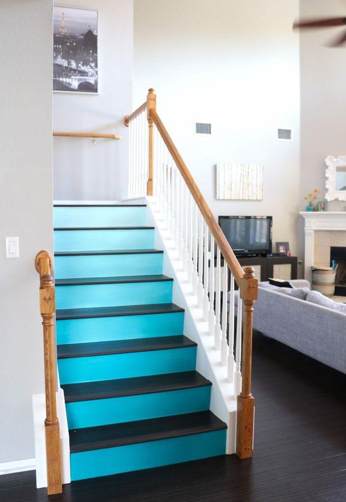 un dégradé de bleu sarcelle sur les contremarches de l'escalier en contraste avec le bois laqué foncé, qui donner de la profondeur à la cage d'escalier