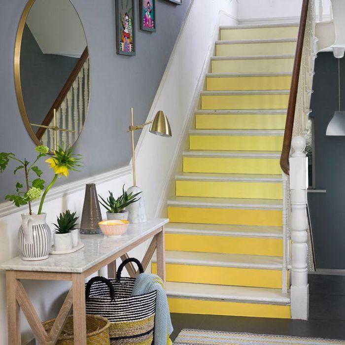 renovation escalier bois, escalier aux contremarches en dégradé de jaune qui illuminent l'entrée couleur bleue grise et s'harmonisent avec les accents déco en laiton