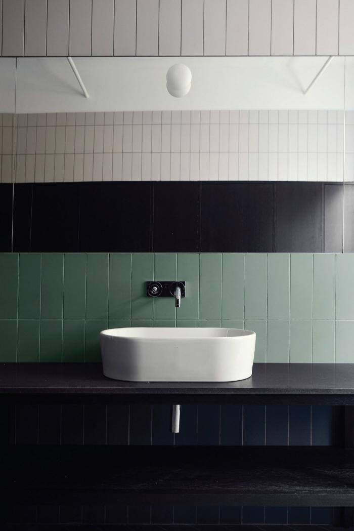 une crédence de salle de bains originale composée de deux rangée de carreaux verts posés horizontalement, une salle de bains où on mélange trois revêtements muraux