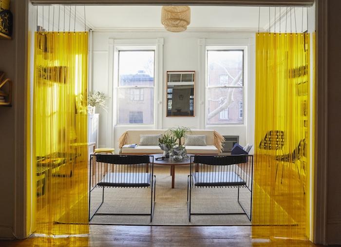 cloison decorative rideau plastique jaune suspendu, canapé beige, chaises metalliques noires, table basse ronde