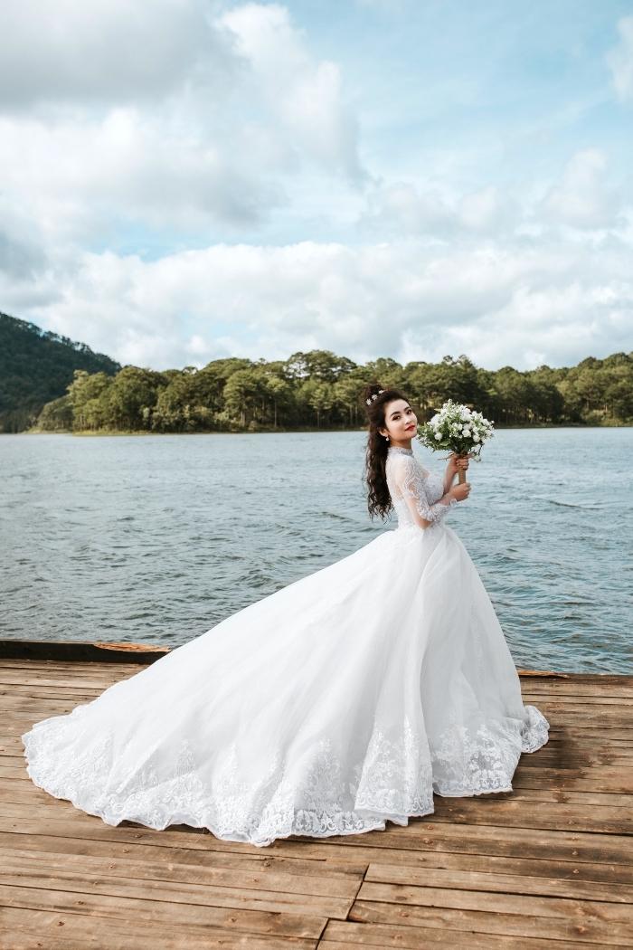 coiffure de mariée aux cheveux mi-attachés avec accessoire de tête, modèle de robe princesse à manches brodées