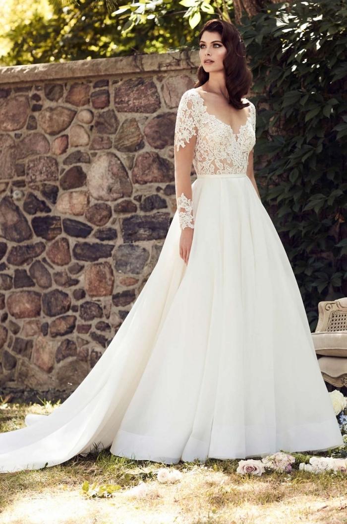 coiffure de mariée aux cheveux bouclés, modèle de robe de mariée à design princesse avec manches transparentes à motifs dentelle