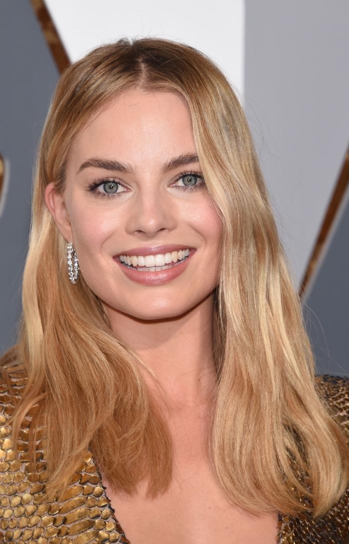 coloration avec meches blondes et racines foncées, coupe de cheveux carré long plongeant, maquillage yeux bleus