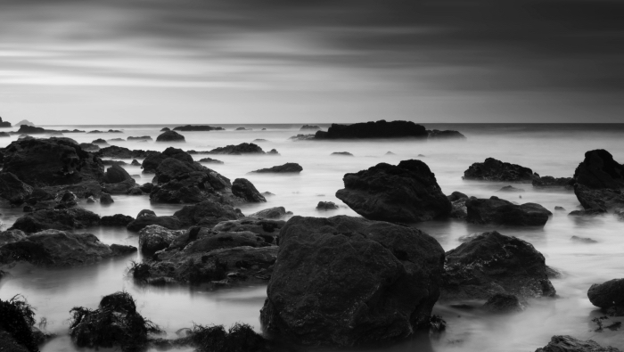 photographie noir et blanc de plage de rochers dans la brume, paysage marin empreint d'un certain mysticisme