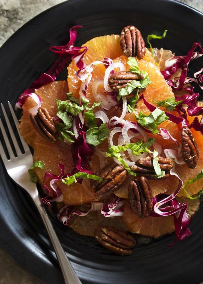 assiette noire, salade simple d'oranges, bandes de choux et de laitue, combiner des fruits avec des légumes verts