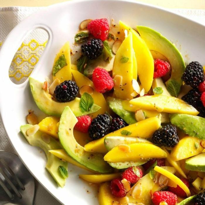 recette d'hiver, salade d'avocats, framboises, myrtilles, feuilles de menthe, disposés sur un plateau blanc
