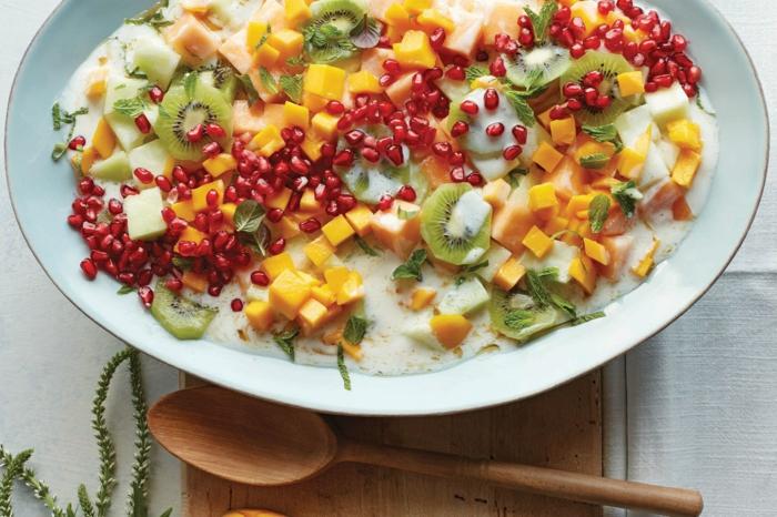 plateau de fruits d'hiver, kiwis, mangue, pommes, salade assaisonné de sauce de salade, cuillère en bois, grande assiette blanche