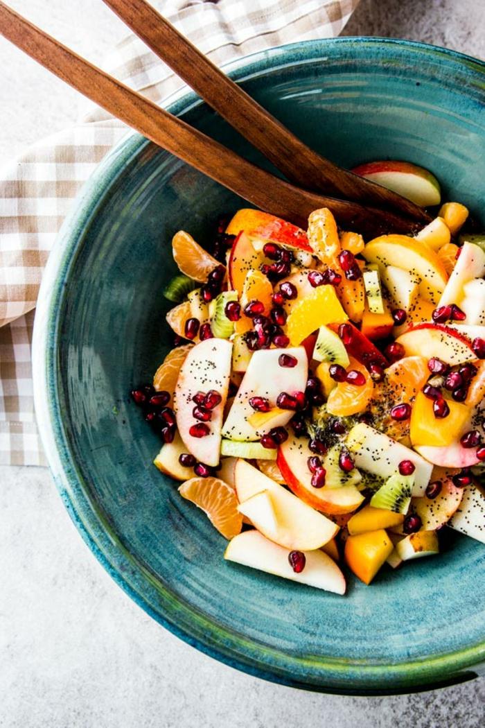 combiner des fruits saisonniers et arranger des salade de fruits frais, deux cuillères de bois, bol bleu