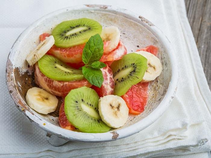 bol de salade d'hiver, kiwis, bananes, pamplemousse, nappe blanche, bananes tranchées, salade fruits frais
