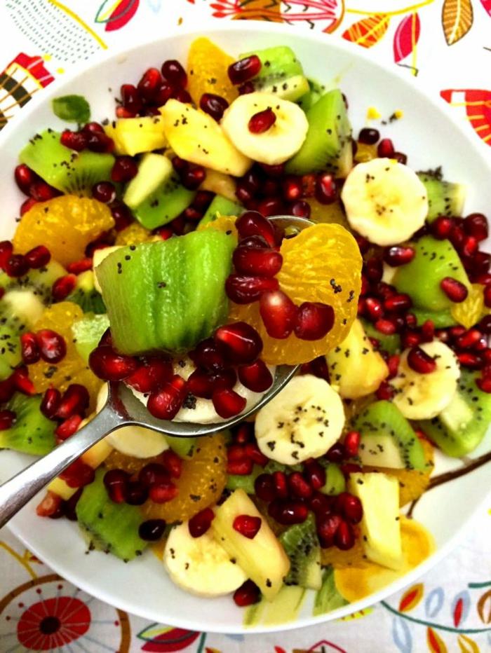 salade fraîche riche en vitamines, kiwi, grenade, bananes, graines de pavot, assiette blanche, nappe aux dessins