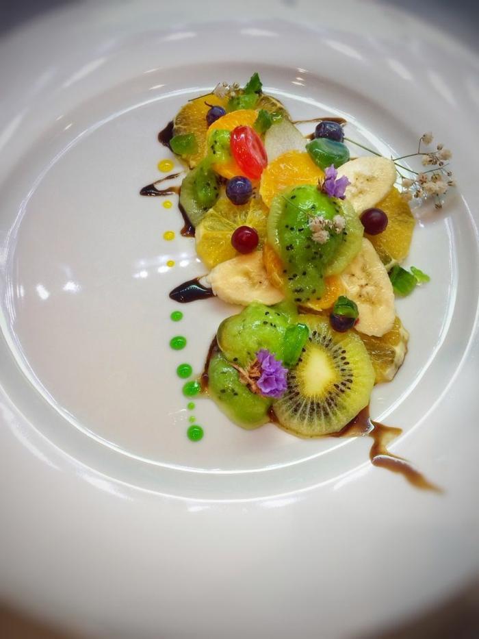 joli arrangement de fruits sur assiette de présentation, gouttes de sirop vert, kiwis tranchés, baies bleues, kiwis, groseilles à maquereau