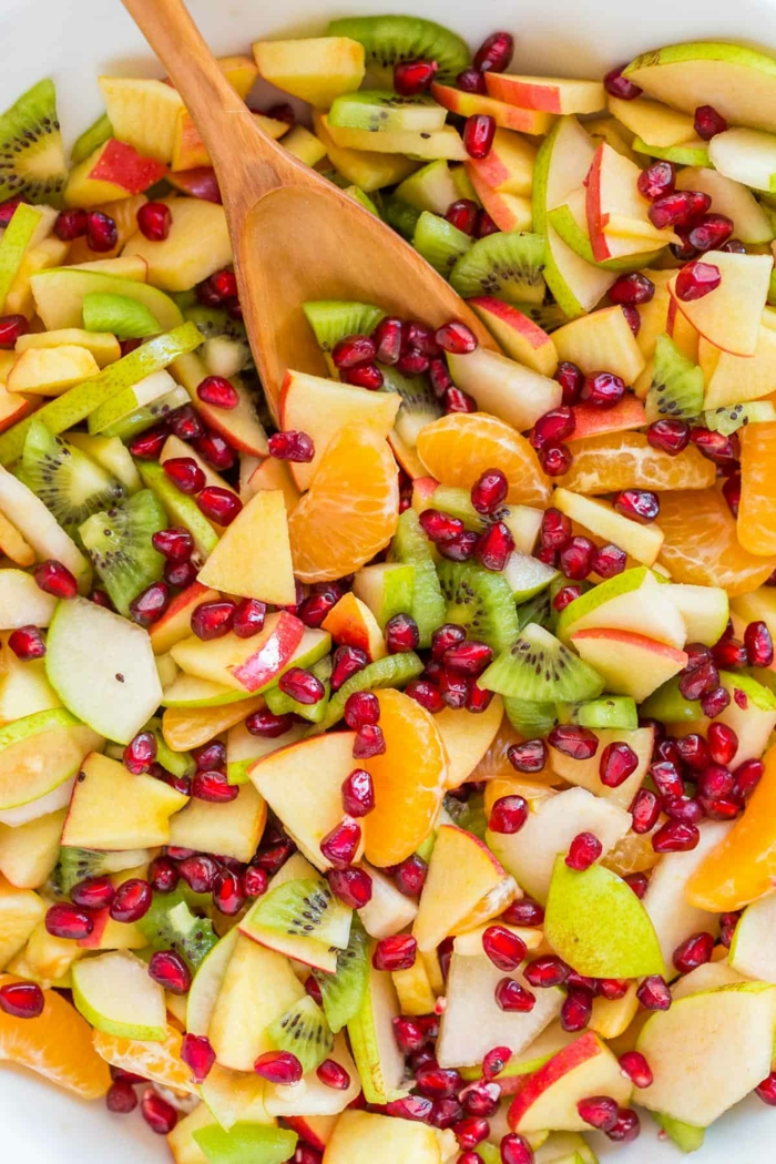 salade de fruits fantastique, cuillère en bois, mandarines, graines de grenade, kiwis, reps de fete pour 20 personnes