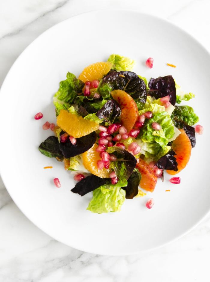 assiette de présentation blanche, salade de fruits, agrumes et de feuilles fraîches, laitue, graines de grenade