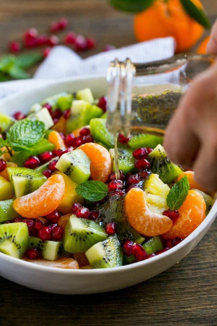 mandarines segmentées, kiwis tranchés, feuilles de menthe, kiwis, graines de grenade arrosés de sirop pour salade de fruits