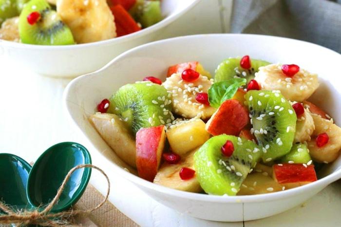plusieurs fruits combinés dans une assiette et parsemés de sésame, rondins de bananes, tranches de pommes, et de kiwis