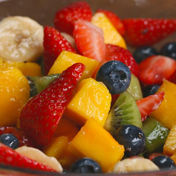 salade fruits, mangue, fraises, bananes, baies bleues, kiwis, salade de fruits découpés et combinés dans un bol
