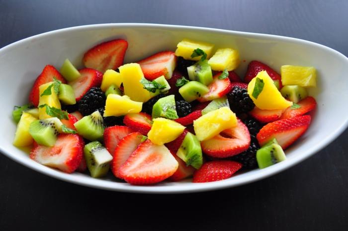 assiette blanche, fraises découpées, kiwis, mangues, myrtilles, salade de fruits frais et décongelés