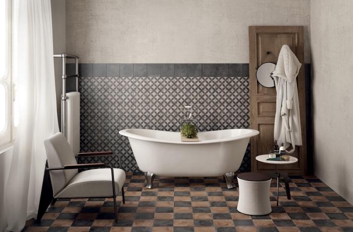 soubassement en carreaux de ciment à motifs graphiques vintage avec bordure noire qui joue le rôle d'une crédence de baignoire