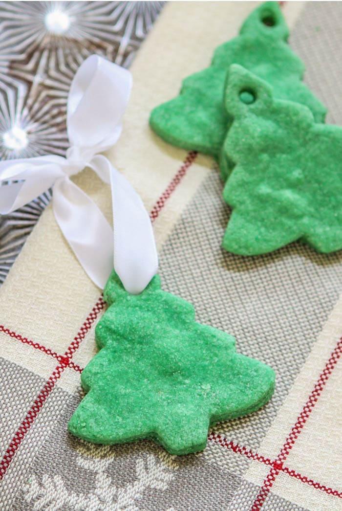 fabriquer décoration de noel en pate à sel en forme de sapin avec peinture et paillettes et ruban blanc satin pour accrocher