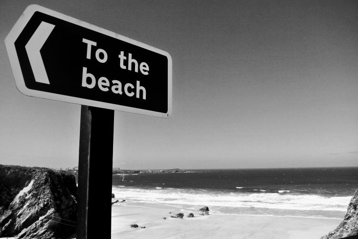 photo noir et blanc d'une plaque directionnelle et de la plage déserte en arrière plan, photographie monochrome