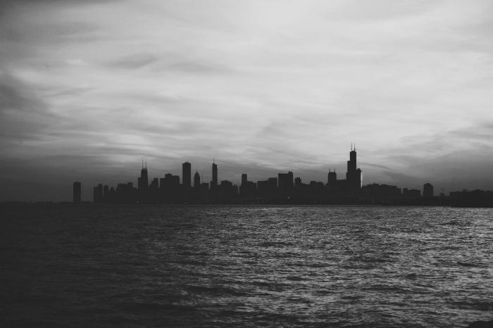 image noir et blanc de silhouette d'une ville se dessinant à l'horizon derrière les eaux calmes de la mer