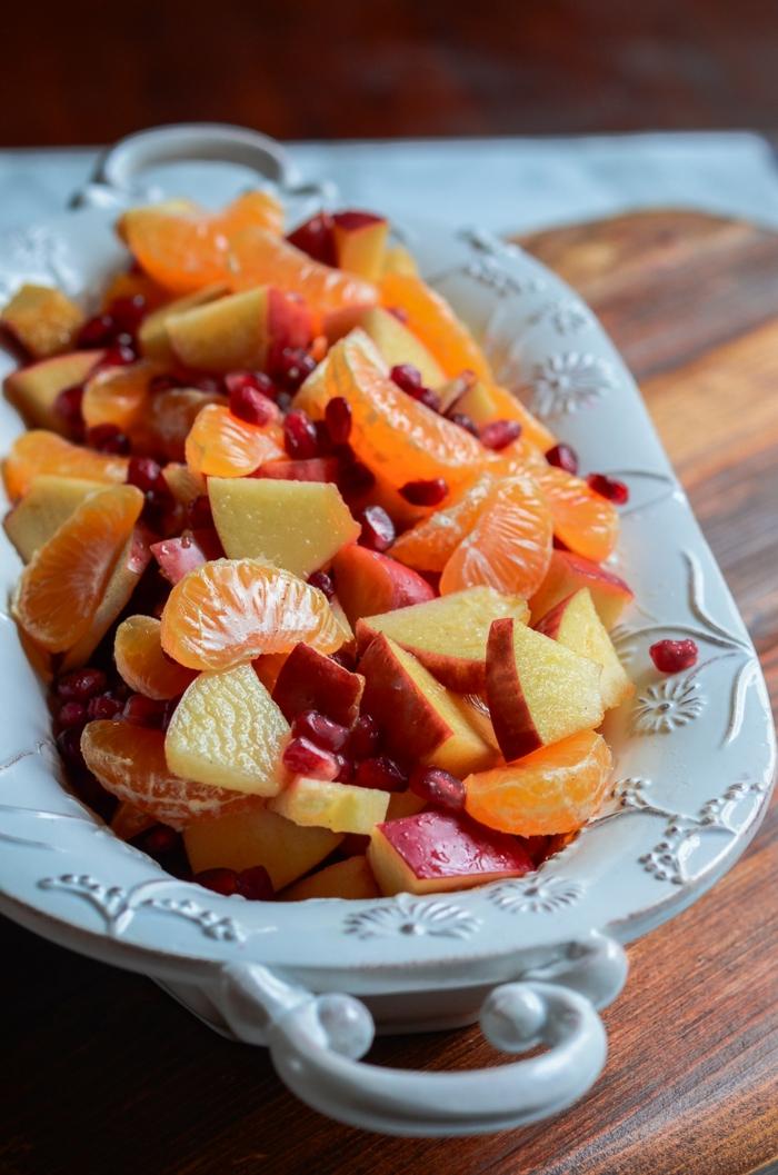 salade de fruits frais, mandarines, pommes, graines de grenade, assiette blanche aux ornements