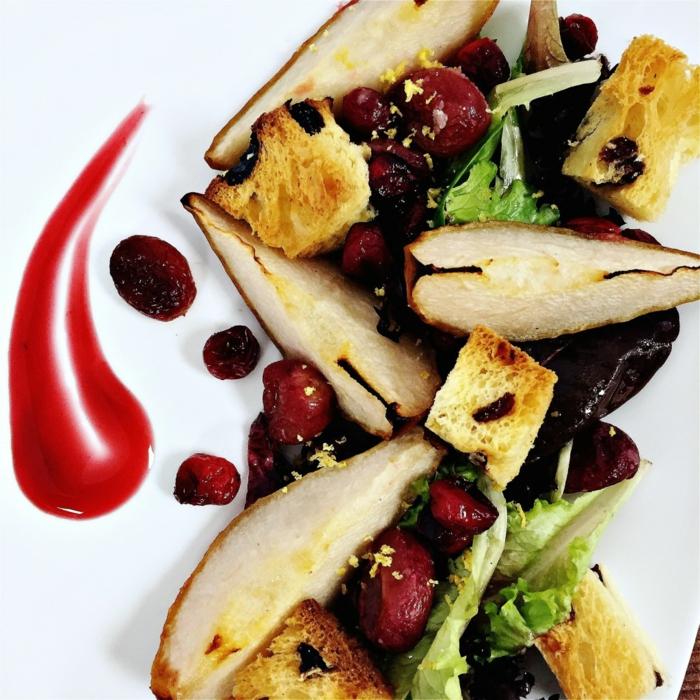 salade de fruits hiver chaude, canneberges séchées, poires, pain grillé en cubes, feuilles de laitue