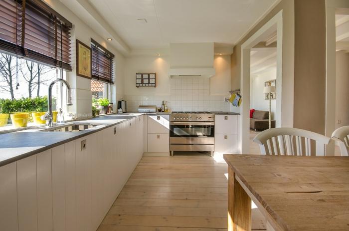 sol cuisine en parquet clair, grande table rustique, chaises blanches, grande fenêtre