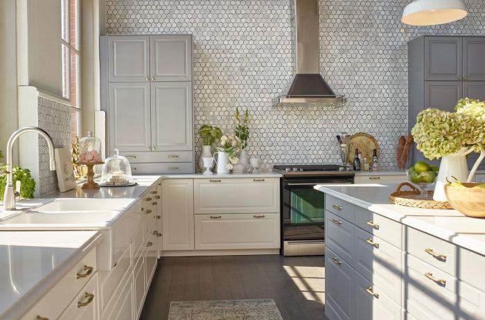 mur en tuiles mosaiques, placards en l, grand îlot en gris et blanc avec tiroirs, cuisinière rétro