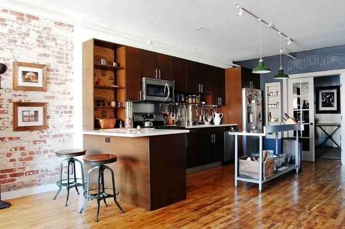 cuisine au sol laqué, tabourets industriels, mur en briques, lampes suspendues vertes, îlot en l