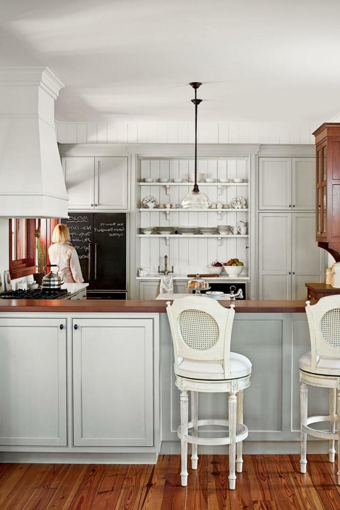 cuisine lambris bois blanc, chaises rétro blanches, sol cuisine bois laqué, tableau mémo noir, étagères