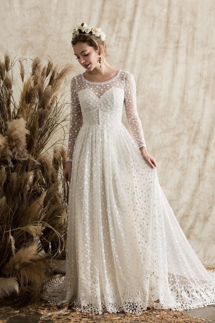 coiffure de mariée aux cheveux attachés en chignon avec couronne de fleurs, modèle de robe longue fluide à effet dentelle
