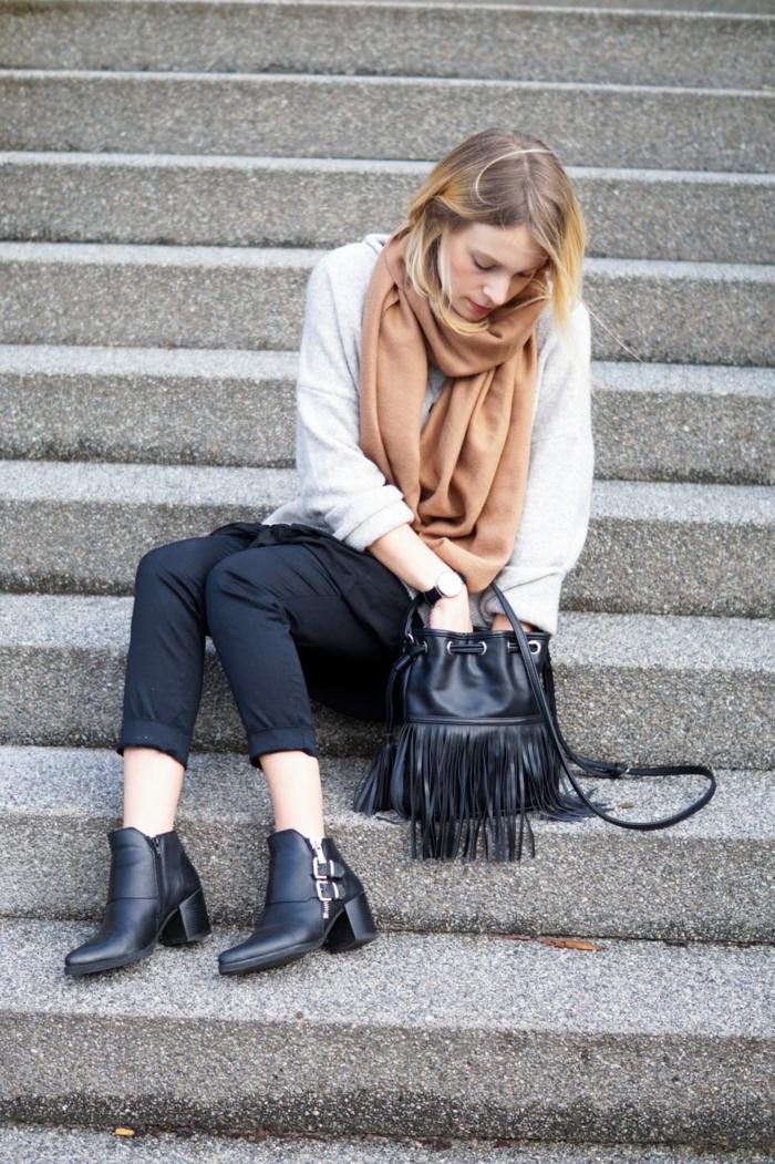 femme assise à l'escalier, bottes noires, pantalon noir, sac noir en cuir, grande écharpe camel, pull chaud femme