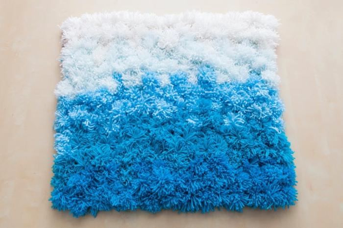 tapis ombré en bleu et blanc, design rectangulaire, pompons aux longs brins, tapis laine en pompons