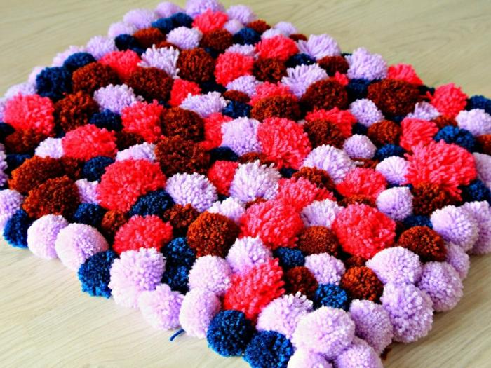 pompons arrangés et assemblés en tapis en pompon rectangulaire, diy tapis de diy pompon