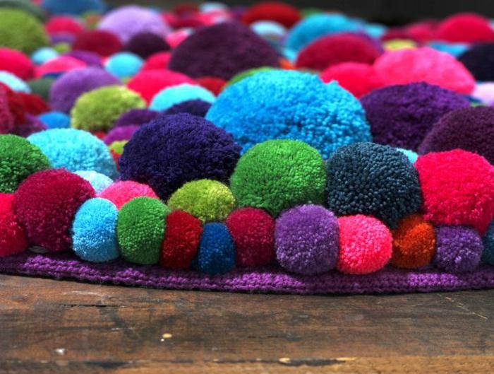 grand tapis de pompons cousus multicolores, base lilas au tricot, sol en planches, pompons de taille variable