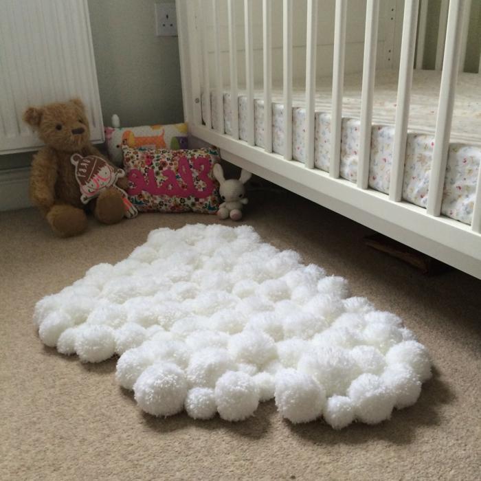 jolie décoration pour la chambre d'enfant, petit tapis blanc forme irrégulière, ourson peluche, coussin mignon et jouets sous le lit de bébé