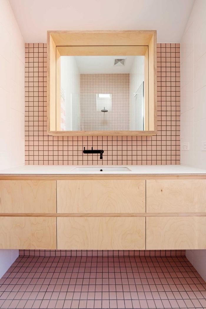 revêtement de sol et mur en carrelage rose pour une salle de bains d'aspect vintage, meuble sous vasque à finition bois naturel associé à un miroir étagère fonctionnelle
