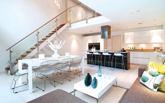 idee de separation cuisine salon avec un ilot central, canapé gris, ilot central noir, facade cuisine blanche, table salle à manger blanche scandinave