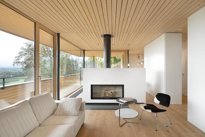 une cheminée de séparation noir et blanc pour séparer un salon avec canapé blanc, parquet bois clair, chaise vache