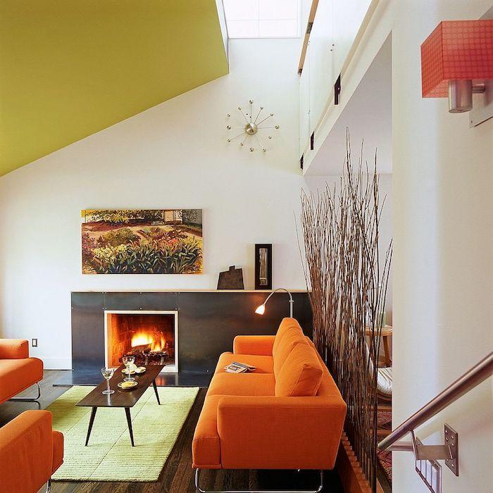 amenagement salon sous pente avec fauteuils et canapé orange, cheminée moderne, table basse bois, parquet marron foncé, separation branches de bois