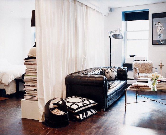 rideau blanc semi transparent pour séparer un salon avec canapé noir, deco graphique, piles de livres, parquet bois foncé