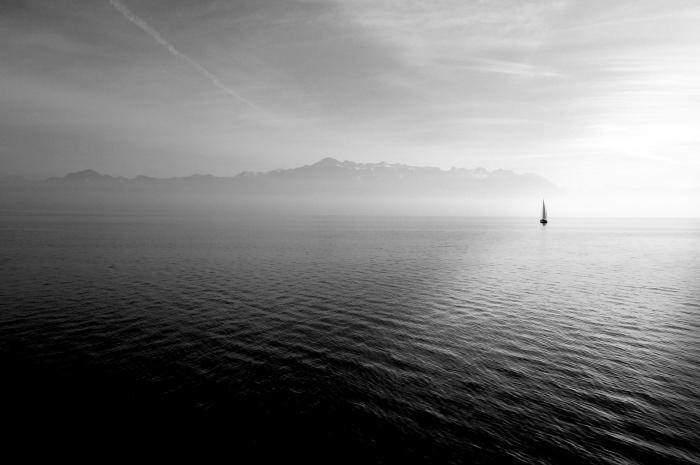 silhouette lointaine d'un voilier nageant dans les eaux calmes de la mer, photographie noir et blanc de paysage marin