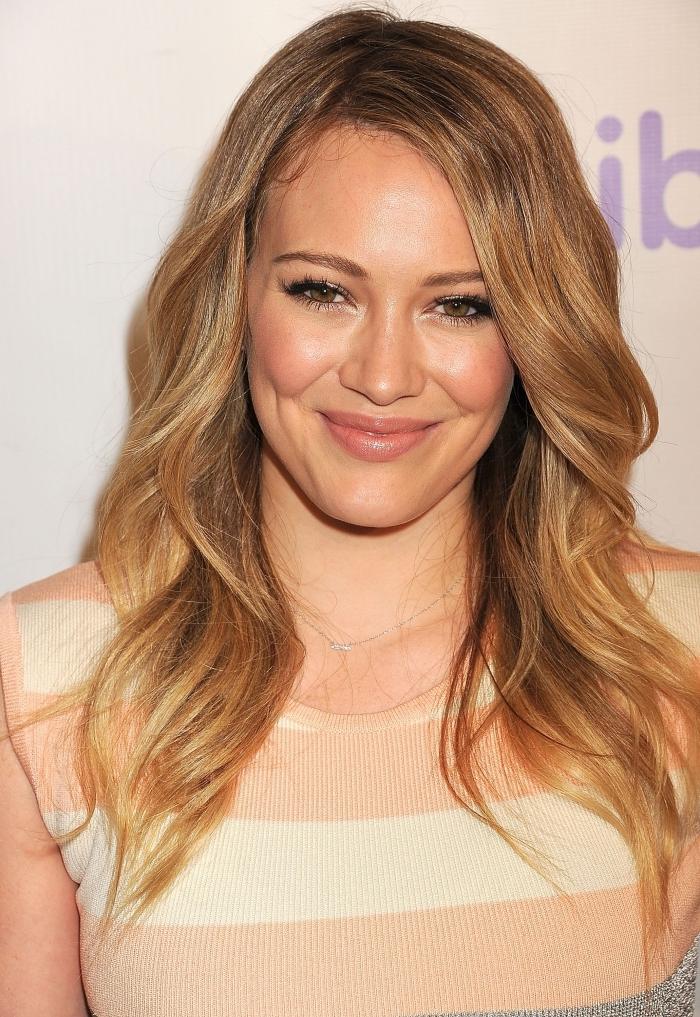 coiffure de célébrité Hilary Duff aux cheveux naturellement bouclés, idée balayage blond sur brunette aux reflets caramel