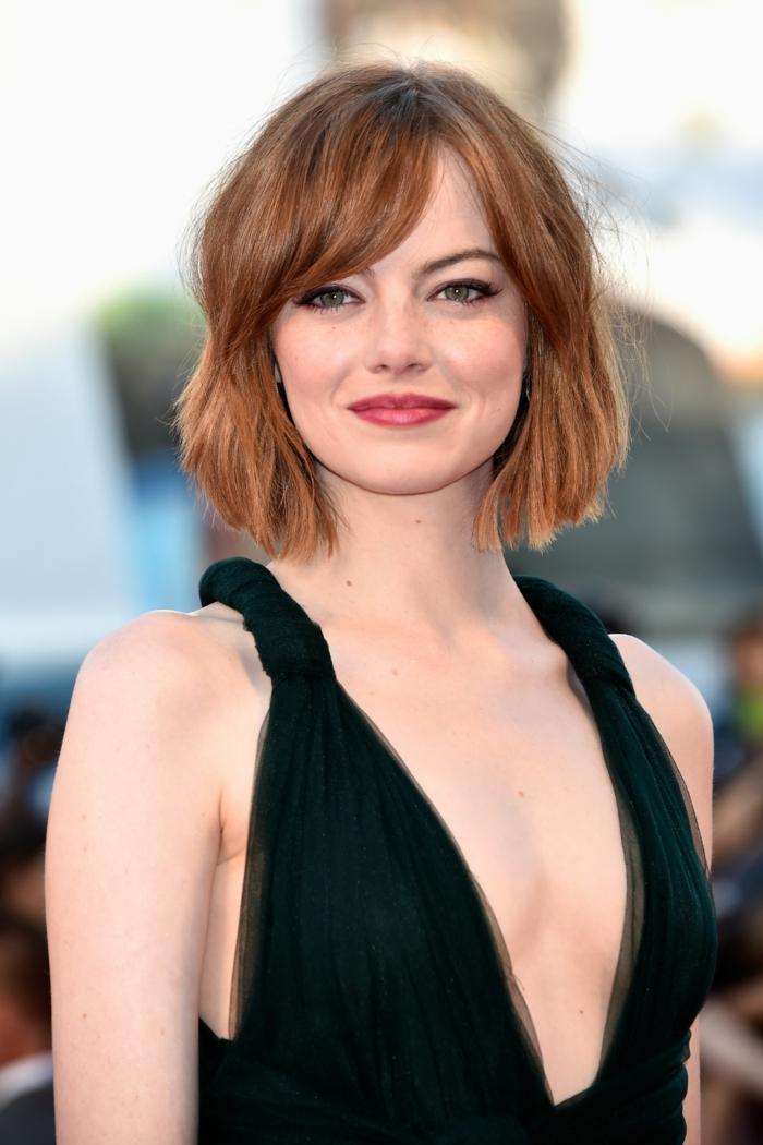 carré plongeant avec frange, frange de côté, Emma Stone portant une robe noire, décolleté plongeant