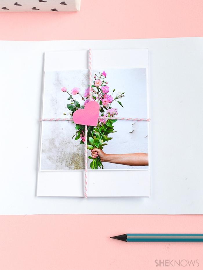 photo imprimée d un bouquet de fleurs sur un bout de papier blanc avec décoration de fils rose et blanc et coeur rose