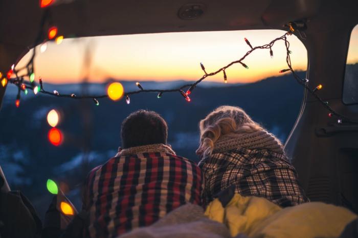 L'intérieur d'un caravane, guirlande lumineuse, couple assise, passer du temps ensemble, image couple amoureux, image st valentin la beauté de l'amour